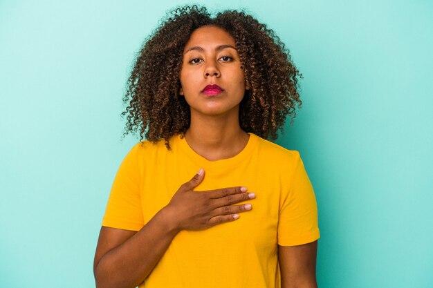 Joven mujer afroamericana con pelo rizado aislado sobre fondo azul tomando un juramento, poniendo la mano en el pecho.