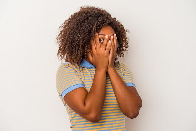 Joven mujer afroamericana con pelo rizado aislado sobre fondo blanco parpadea entre los dedos asustada y nerviosa.