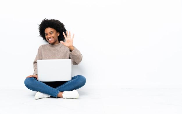 Joven mujer afroamericana con un portátil sentado en el suelo contando cinco con los dedos