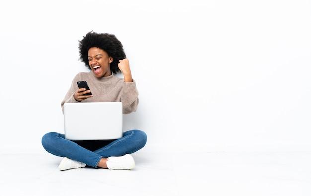 Joven mujer afroamericana con un portátil sentado en el suelo con el teléfono en posición de victoria