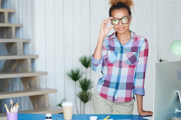 Joven mujer afroamericana posando en el escritorio