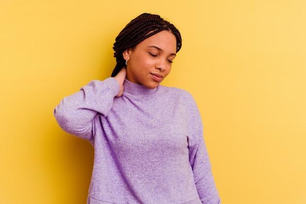 Joven mujer afroamericana que tiene dolor de cuello debido al estrés, masajeando y tocándolo con la mano.
