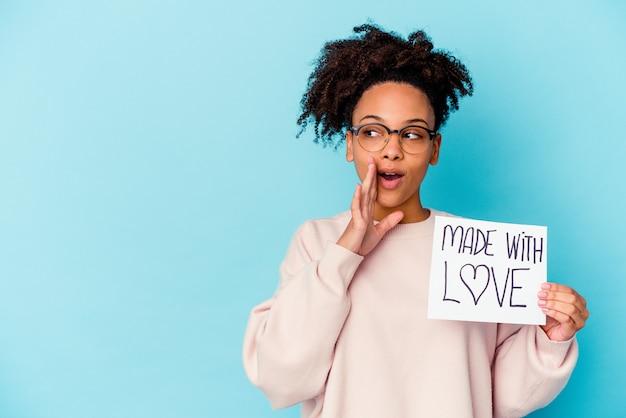 Joven mujer afroamericana de raza mixta sosteniendo un concepto hecho con amor está diciendo una noticia secreta de frenado en caliente y mirando a un lado