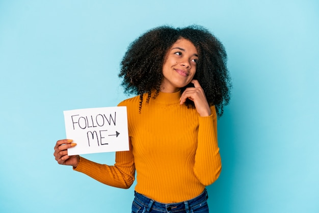 Joven mujer afroamericana rizada sosteniendo un cartel de sígueme soñando con lograr metas y propósitos