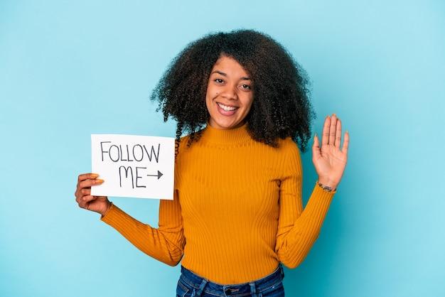 Joven mujer afroamericana rizada sosteniendo un cartel de sígueme sonriendo alegre mostrando el número cinco con los dedos.