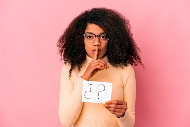 Joven mujer afroamericana rizada sosteniendo un interrogatorio en un cartel que guarda un secreto o pide silencio.