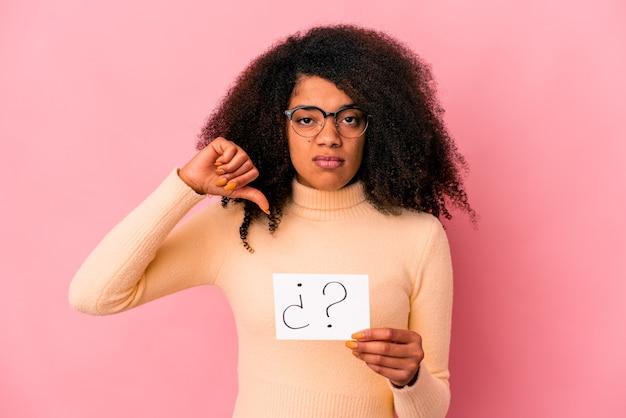 Joven mujer afroamericana rizada sosteniendo un interrogatorio en un cartel que muestra un gesto de aversión, pulgares hacia abajo. concepto de desacuerdo.