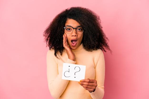 Joven mujer afroamericana rizada sosteniendo un interrogatorio en un cartel sorprendido y consternado.