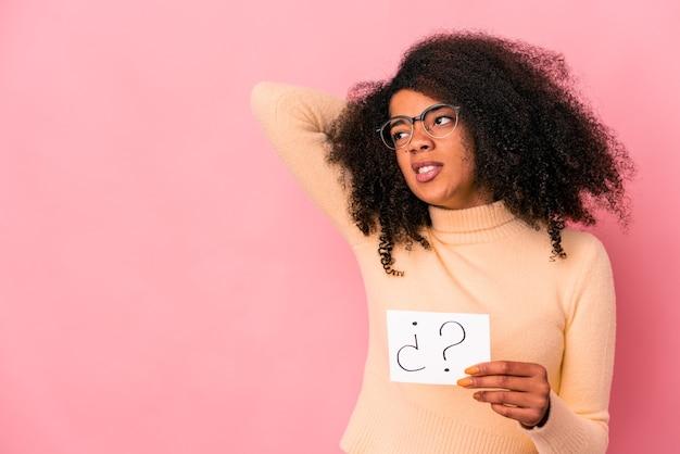 Joven mujer afroamericana rizada sosteniendo un interrogatorio en un cartel tocando la parte posterior de la cabeza, pensando y tomando una decisión.