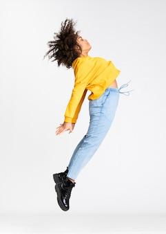 Joven mujer afroamericana saltando sobre la pared blanca