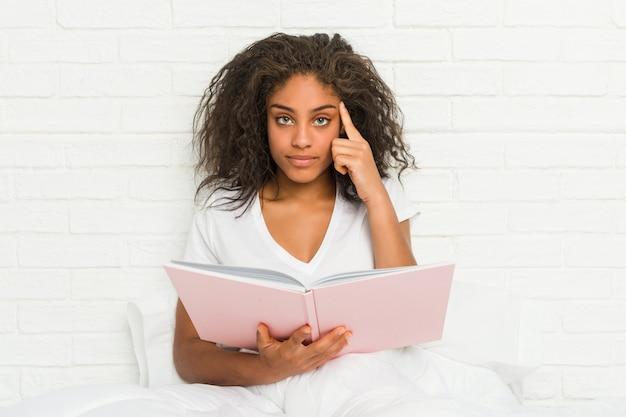 Joven mujer afroamericana sentada en la cama estudiando señalando su sien con el dedo, pensando, centrado en una tarea.