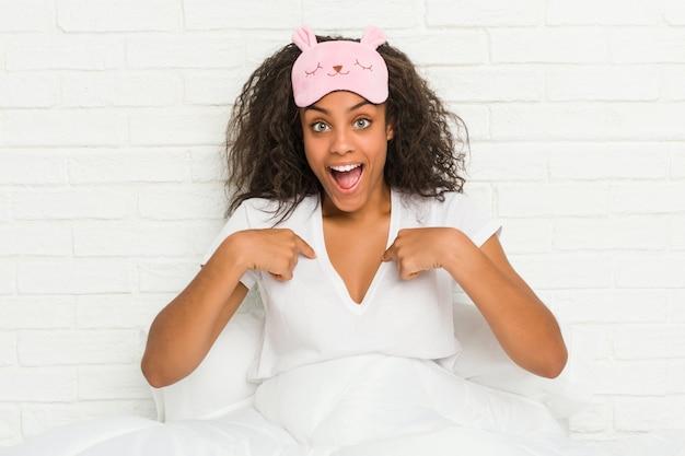 Joven mujer afroamericana sentada en la cama con una máscara para dormir sorprendido apuntando a sí mismo