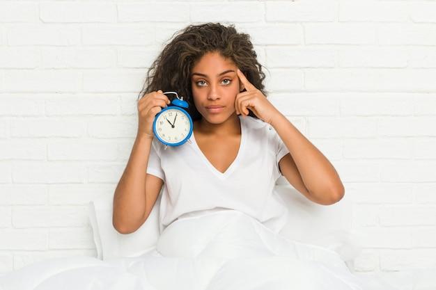Joven mujer afroamericana sentada en la cama sosteniendo un reloj despertador señalando su sien con el dedo, pensando, centrado en una tarea.