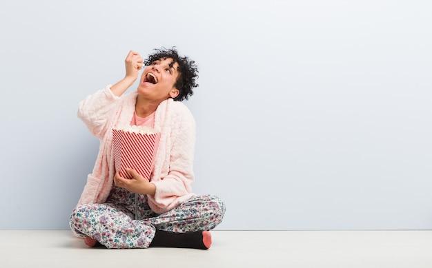 Joven mujer afroamericana sentada sosteniendo una caja de palomitas de maíz