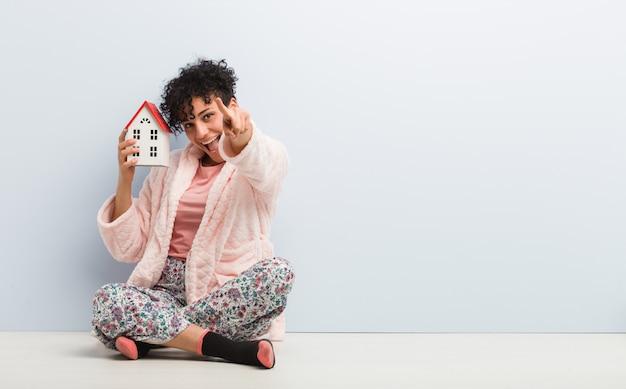 Joven mujer afroamericana sentada sosteniendo un icono de la casa