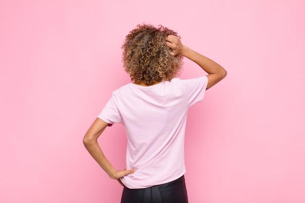 Joven mujer afroamericana sintiéndose desorientada y confundida, pensando en una solución, con la mano en la cadera y otra en la cabeza, vista trasera contra la pared rosa