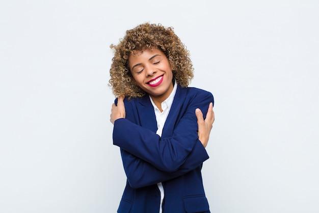 Joven mujer afroamericana sintiéndose enamorada, sonriendo, abrazándose y abrazándose, manteniéndose soltera, siendo egoísta y egocéntrica contra la pared