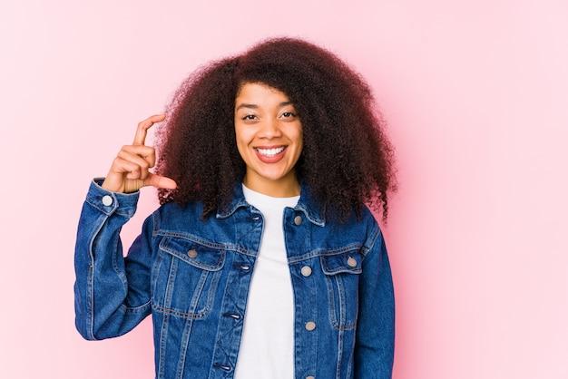 Joven mujer afroamericana sosteniendo algo poco con los dedos índices, sonriente y confiado.