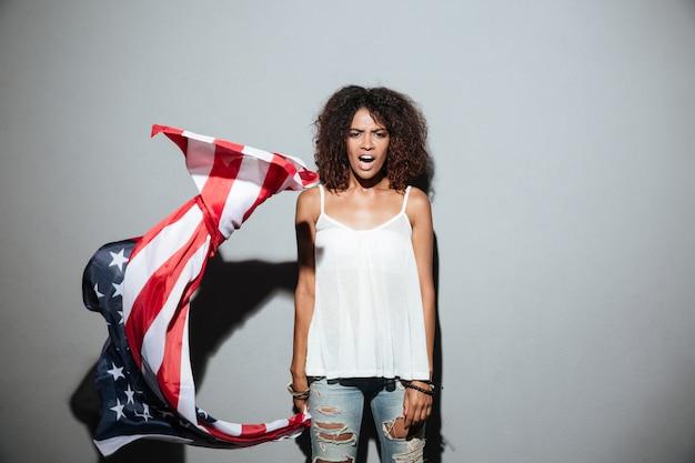 Joven mujer afroamericana sosteniendo la bandera americana y gritando