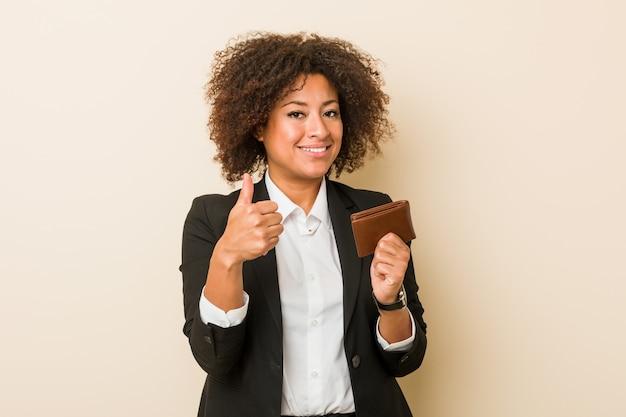 Joven mujer afroamericana sosteniendo una billetera sonriendo y levantando el pulgar