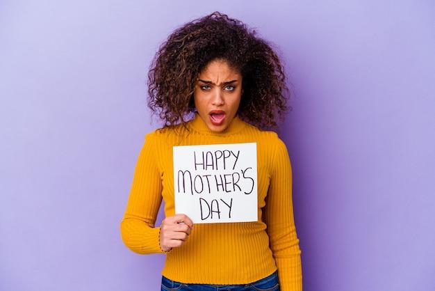Joven mujer afroamericana sosteniendo un cartel de feliz día de la madre aislado gritando muy enojado y agresivo.