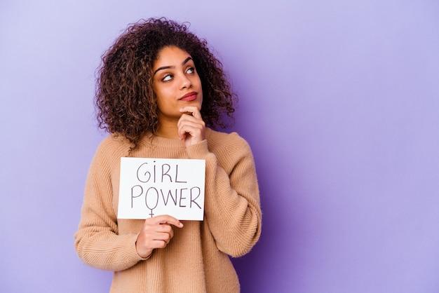 Joven mujer afroamericana sosteniendo un cartel de girl power aislado sobre fondo púrpura mirando hacia los lados con expresión dudosa y escéptica.