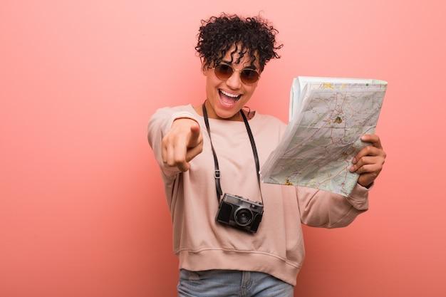 Joven mujer afroamericana sosteniendo un mapa sonrisas alegres apuntando al frente.