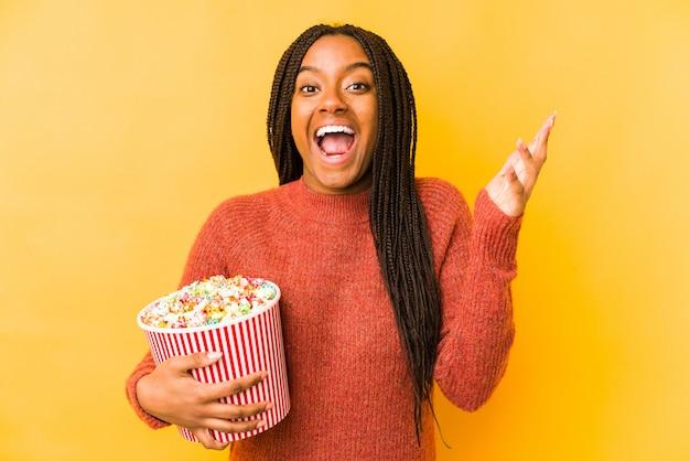Joven mujer afroamericana sosteniendo una palomitas de maíz aislado recibiendo una sorpresa agradable, emocionado y levantando las manos.