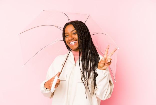 Joven mujer afroamericana sosteniendo un paraguas alegre y despreocupado mostrando un símbolo de paz con los dedos.