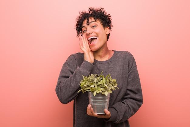 Joven mujer afroamericana sosteniendo una planta gritando emocionado al frente.