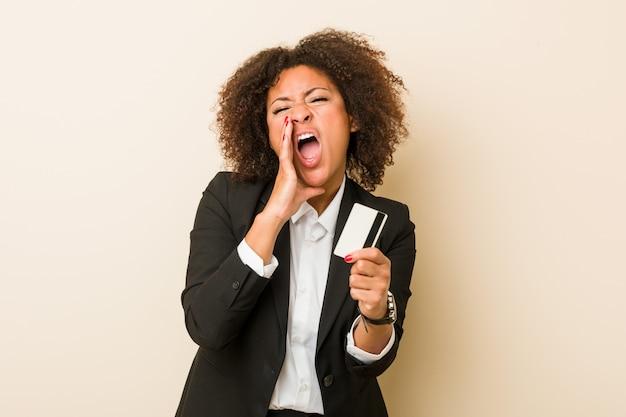 Joven mujer afroamericana sosteniendo una tarjeta de crédito gritando emocionado al frente.