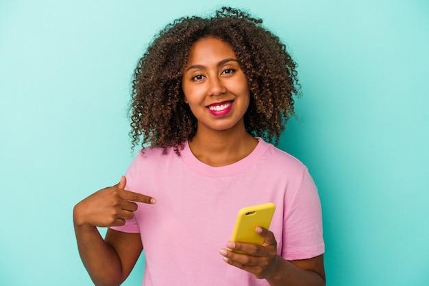 Joven mujer afroamericana sosteniendo un teléfono móvil aislado sobre fondo azul persona apuntando con la mano a un espacio de copia de camisa, orgulloso y seguro