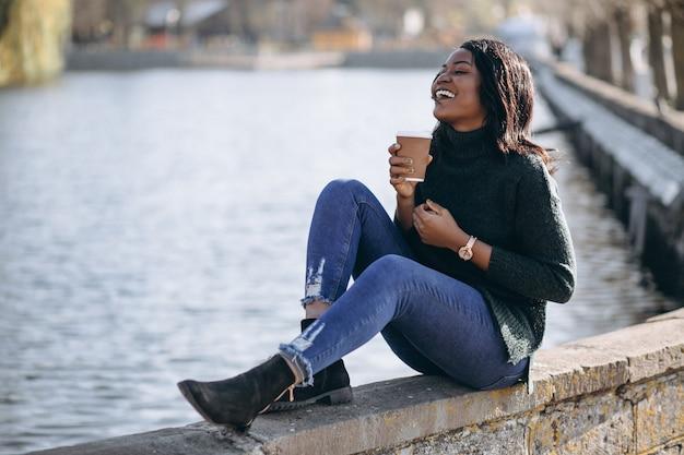 Joven mujer afroamericana tomando café junto al lago