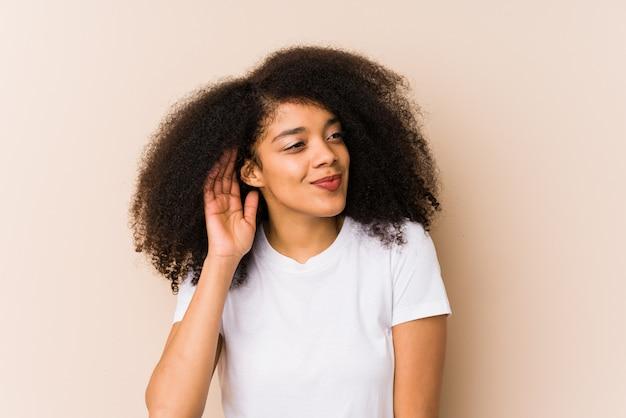 Joven mujer afroamericana tratando de escuchar un chisme.