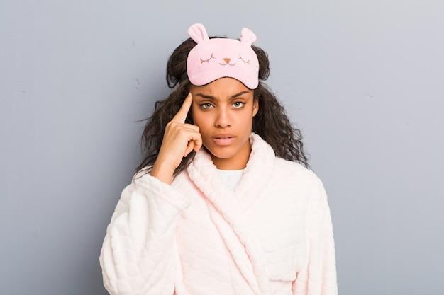 Joven mujer afroamericana vistiendo un pijama y una máscara para dormir apuntando su sien con el dedo, pensando, centrado en una tarea.