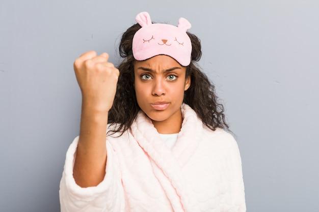 Joven mujer afroamericana vistiendo un pijama y una máscara para dormir mostrando el puño a la cámara, expresión facial agresiva.
