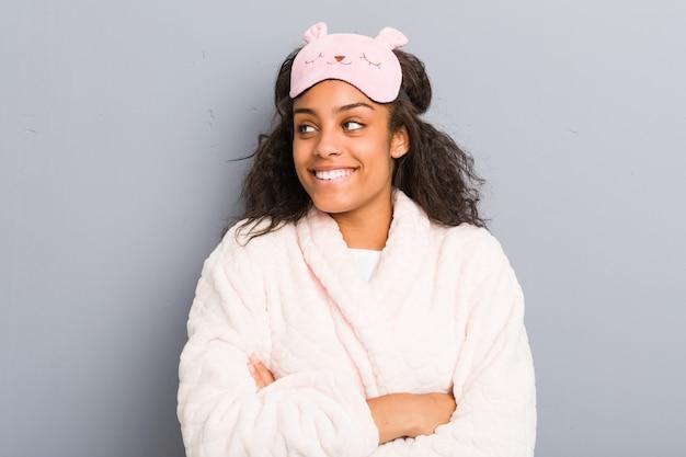 Joven mujer afroamericana vistiendo un pijama y una máscara para dormir sonriendo confiados con los brazos cruzados.