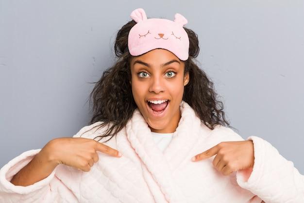 Joven mujer afroamericana vistiendo un pijama y una máscara para dormir sorprendida apuntando a sí misma