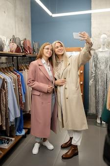 Joven mujer alegre con smartphone haciendo selfie con su madre mientras ambos de pie en boutique entre bastidores con ropa nueva