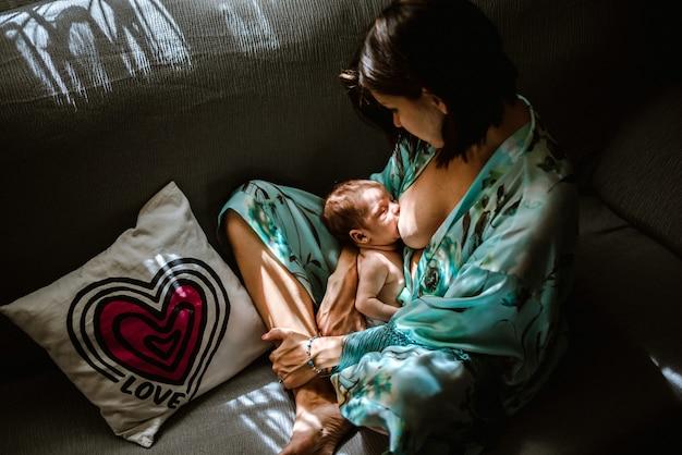 Joven mujer amamantando a su bebé en casa