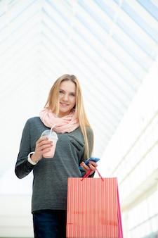 Joven, mujer, ambulante, centro comercial, hacer, llamada, smartphone, tenencia, bolsos, bebida