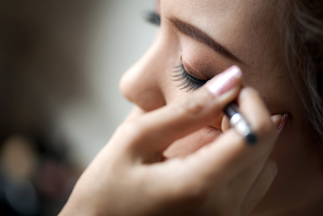 Joven mujer aplicada delineador de ojos.