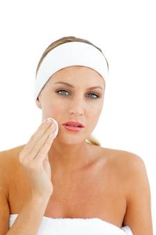 Joven mujer aplicando una base de maquillaje