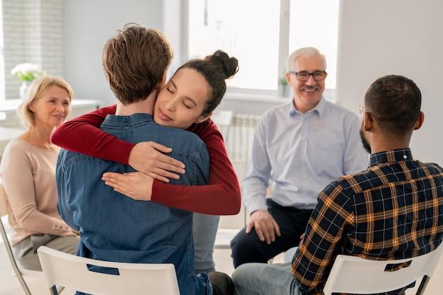 Joven mujer de apoyo abrazando a uno de los compañeros de grupo de sesión psicológica después de discutir sus problemas