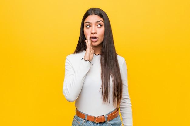Joven mujer árabe bonita contra un amarillo está diciendo una noticia secreta de frenado en caliente y mirando a un lado