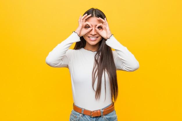 Joven mujer árabe bonita contra un amarillo que muestra signo bien sobre los ojos