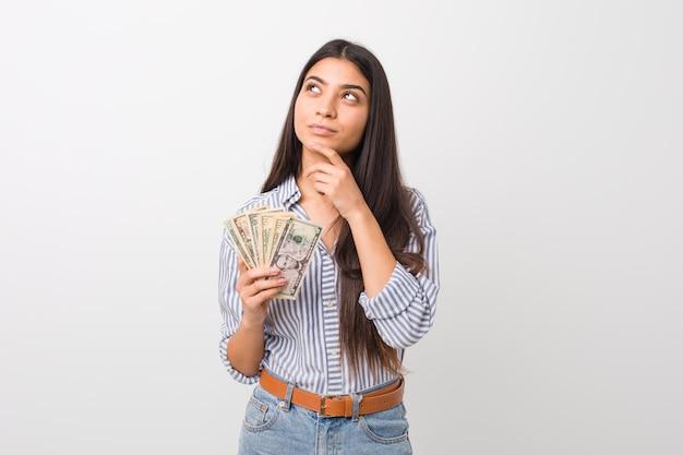 Joven mujer árabe con dólares mirando hacia los lados con expresión dudosa y escéptica.