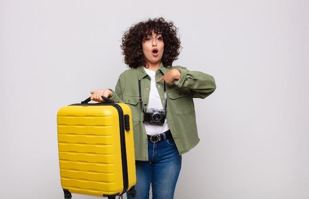 Joven mujer árabe mirando conmocionado y sorprendido con la boca abierta, apuntando al concepto de auto viaje