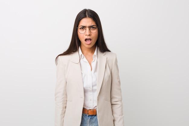 Joven mujer árabe de negocios aislada contra una pared blanca gritando muy enojado y agresivo.