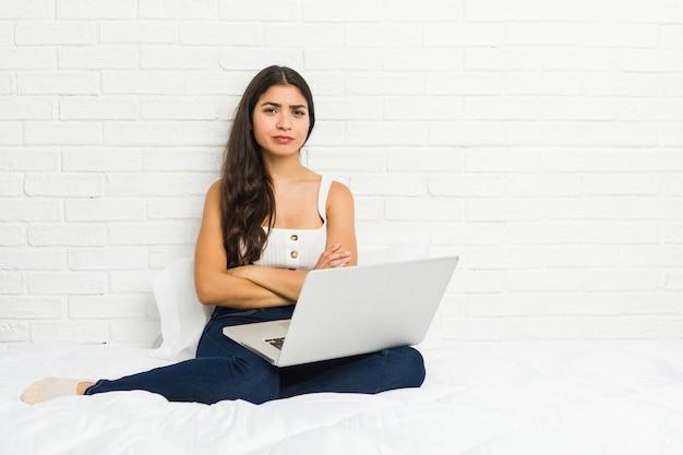Joven mujer árabe que trabaja con su computadora portátil en la cama mirando infeliz con expresión sarcástica.